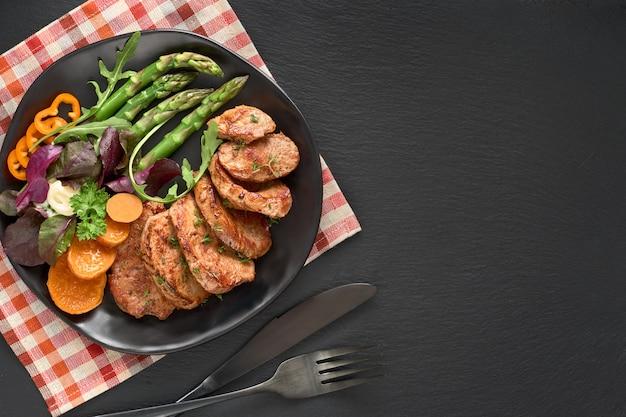 Gebratene scheiben rindfleisch, süßkartoffel und gemischter salat auf schwarzer platte stellten für mahlzeit auf dunklem schiefer ein