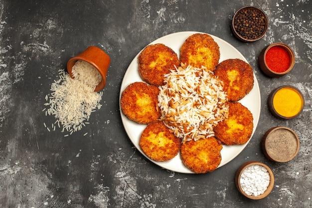 Gebratene schnitzel der draufsicht mit gekochtem reis und gewürzen auf dunklem oberflächenfoto-nahrungsmittelfleischgericht