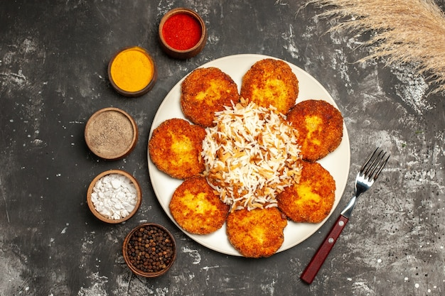 Gebratene schnitzel der draufsicht mit gekochtem reis und gewürzen auf dunklem oberflächenfuttergericht-fotofleisch