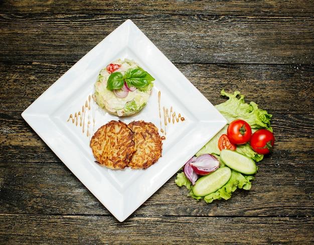 Gebratene schnitzel mit salat garniert mit sahne