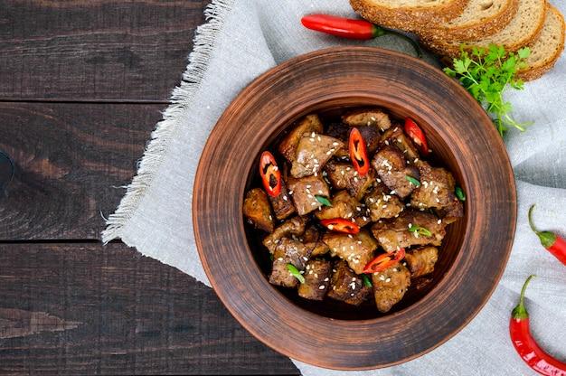 Gebratene schweinefleischstücke mit chili in einer tonschale auf einem dunklen holztisch. draufsicht