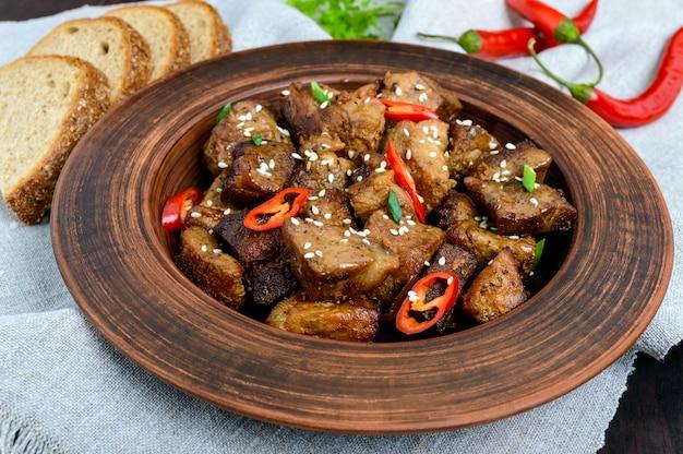 Gebratene schweinefleischstücke mit chili in einer tonschale auf einem dunklen holztisch.