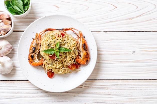 Gebratene spaghetti mit gegrillten garnelen und tomaten