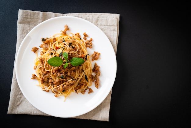 Gebratene spaghetti mit gehacktem schweinefleisch und basilikum