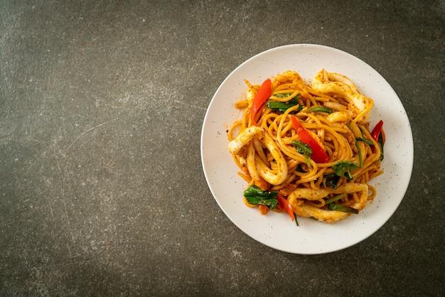 Gebratene spaghetti mit gesalzenem ei und tintenfisch - fusion food style