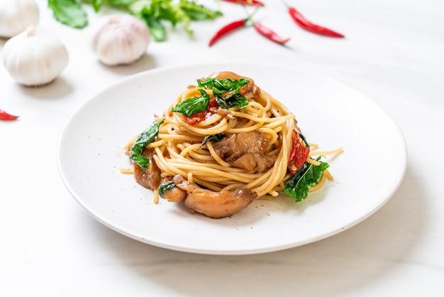 Gebratene spaghetti mit hähnchen und basilikum