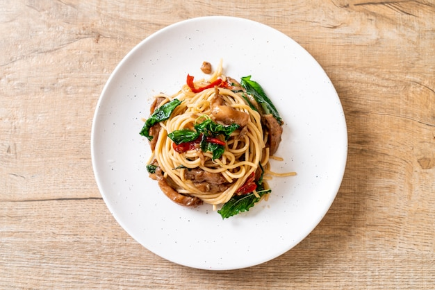 Gebratene spaghetti mit hühnchen und basilikum