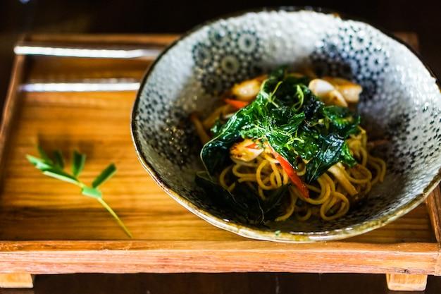 Gebratene spaghetti mit meeresfrüchten und pikanter sauce.