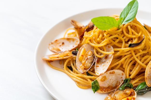 Gebratene spaghetti mit muscheln, knoblauch und chili umrühren