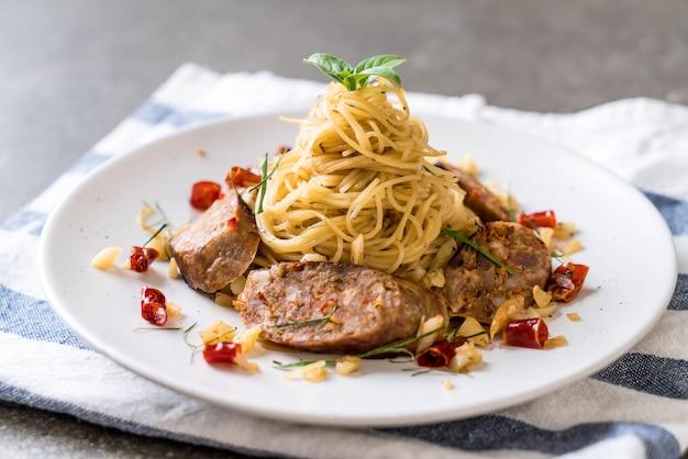 Gebratene spaghetti mit sai aua (nordthailändische pikantwurst) umrühren