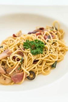 Gebratene spaghetti mit speck und knoblauch