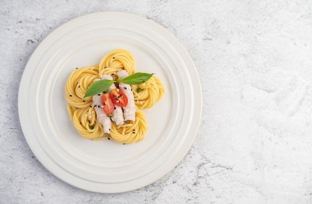 Gebratene spaghetti und schweinefleisch, wunderschön in einem weißen teller angeordnet.