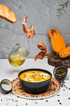 Gebratene speckscheiben, gebratenes brot und rosmarin fallen in eine schüssel kürbissuppe