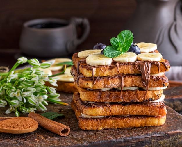 Gebratene stücke weißbrot in einem ei mit milch und mit schokolade bestrichen, french toast