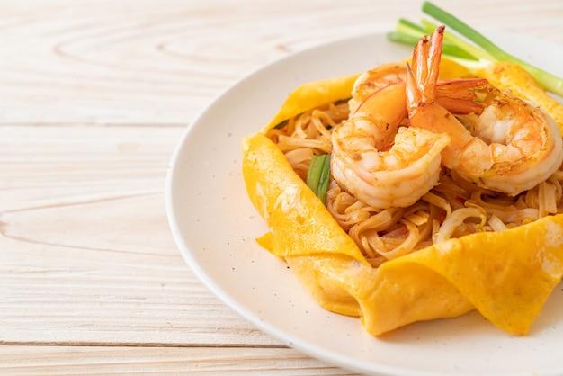 Gebratene thai-nudeln mit garnelen und eierwickel (pad thai) - thailändische küche