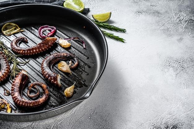 Gebratene tintenfischtentakeln mit rosmarin, knoblauch und butter in einer pfanne
