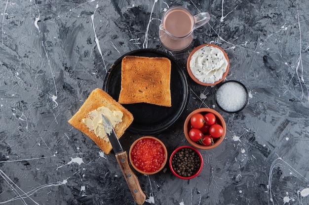 Gebratene toasts mit frischen roten kirschtomaten auf marmortisch.