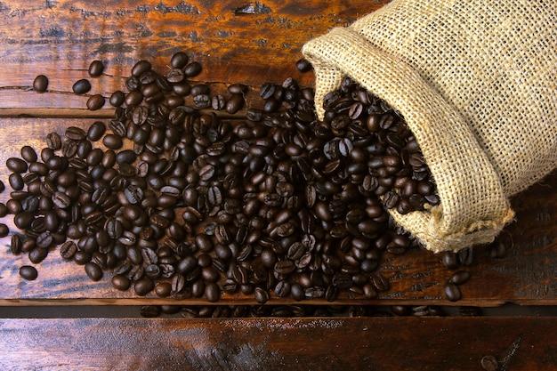 Gebratene und frische kaffeebohnen innerhalb der rustikalen gewebetasche und gegossen über rustikalen holztisch. draufsicht