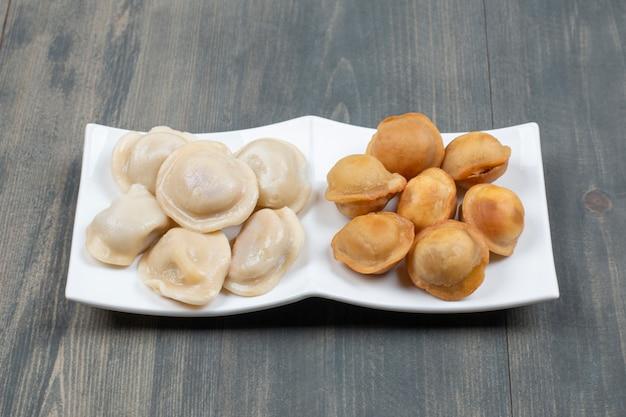Gebratene und gekochte köstliche knödel in einem weißen teller