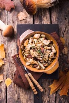 Gebratene waldpilze, steinpilze, zwiebeln. rustikaler teller in einer bratpfanne, vegetarisches herbstlebensmittel auf ansicht