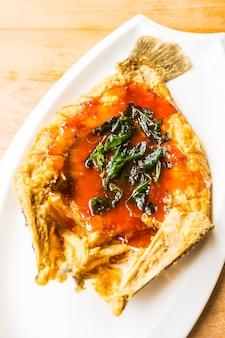 Gebratene Wolfsbarschfische in der weißen Platte mit würziger und süßer Soße