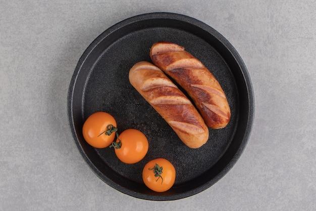 Gebratene würstchen und tomaten auf schwarzem teller.