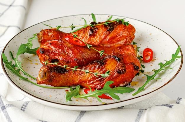 Gebratene würzige hähnchenschenkel oder drumsticks auf einem weißen teller. köstliches dinner- oder lunch-konzept.