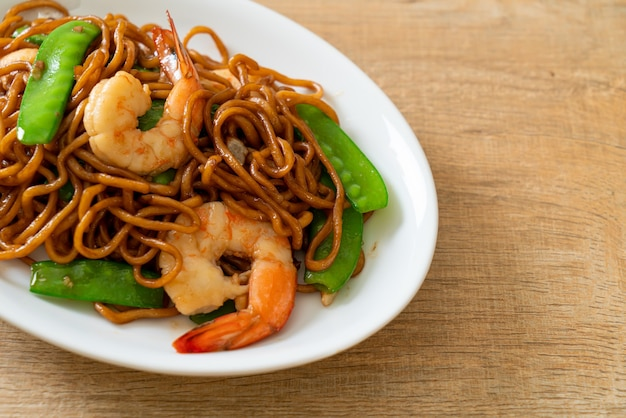 Gebratene yakisoba-nudeln mit grünen erbsen und shrimps - asiatische küche