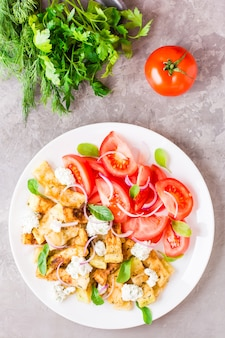 Gebratene zucchini mit feta, tomaten, kräutern und zwiebeln auf einem teller