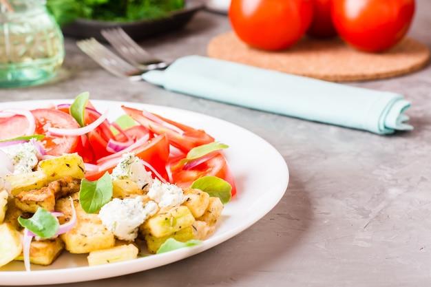 Gebratene zucchini mit feta, tomaten, kräutern und zwiebeln auf einer platte auf einer tabelle