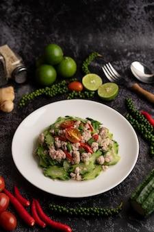 Gebratene zucchini mit gehacktem schweinefleisch in weißem teller umrühren