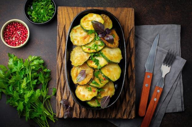 Gebratene zucchini mit paprika, basilikum und petersilie in einer gusseisenpfanne auf einer alten dunklen oberfläche. selektiver fokus. draufsicht.