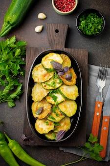 Gebratene zucchini mit paprika, basilikum und petersilie in einer gusseisernen pfanne auf altem dunklem hintergrund.