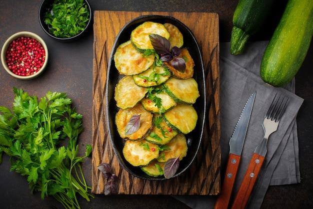 Gebratene zucchini mit paprika, basilikum und petersilie in einer gusseisernen pfanne auf einer alten dunklen oberfläche