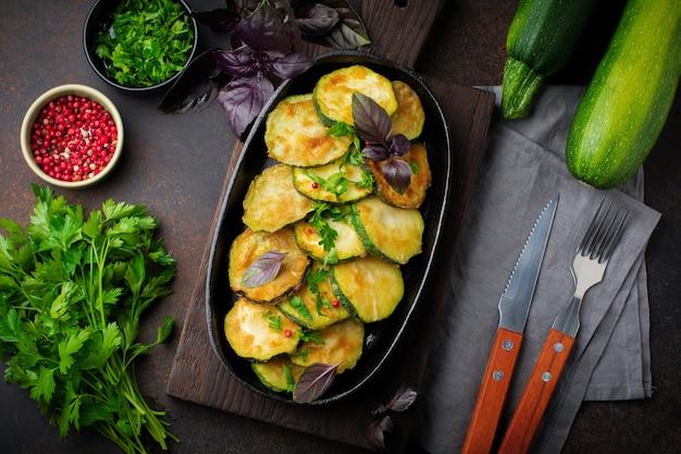 Gebratene zucchini mit paprika, basilikum und petersilie in einer pfanne aus gusseisen auf einer alten dunklen oberfläche