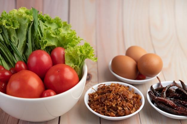 Gebratene zwiebeln, paprika, eier, tomaten, salat und frühlingszwiebeln in einer weißen tasse auf einem holzboden.