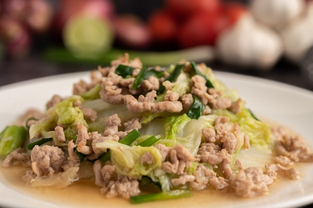 Gebratenen chinakohl mit gehacktem schweinefleisch in weißer schüssel umrühren.