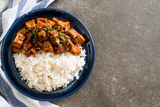 Gebratenen tofu mit pikanter sauce auf reis rühren