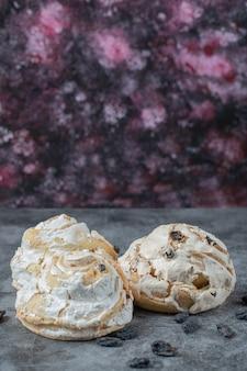 Gebratener baiser-keks mit schwarzen rosinen und weißer schokolade oben auf dem marmortisch.