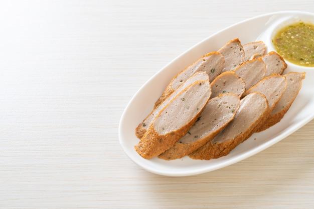 Gebratener chinesischer fischkuchen oder fischbällchen, geschnitten mit würziger meeresfrüchte-dip-sauce