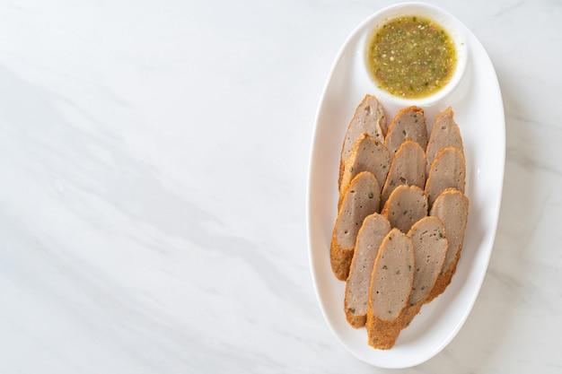 Gebratener chinesischer fischkuchen oder fischbällchen in scheiben geschnitten mit würziger meeresfrüchte-dip-sauce