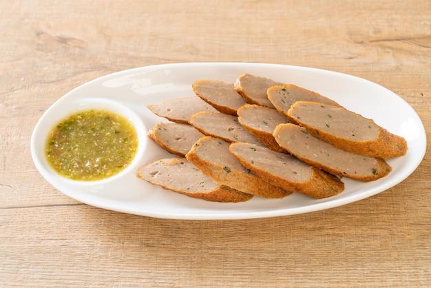 Gebratener chinesischer fischkuchen oder fischbällchen in scheiben geschnitten mit würziger meeresfrüchte-dip