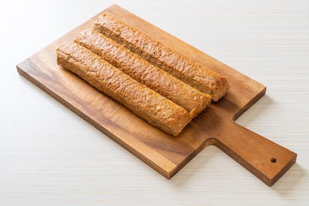 Gebratener chinesischer fischkuchen oder fischballlinie auf holzbrett
