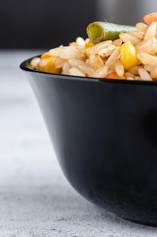 Gebratener chinesischer gemüsereis und eier, die in einer schüssel mit stäbchen serviert werden. chinesische küche