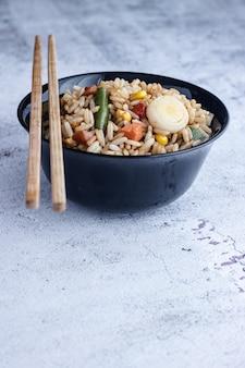 Gebratener chinesischer gemüsereis und eier serviert in einer schüssel mit stäbchen. chinesische küche