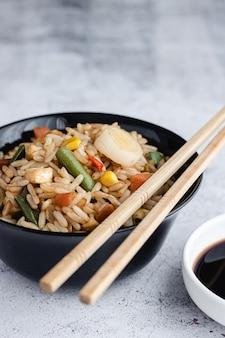 Gebratener chinesischer gemüsereis und eier serviert in einer schüssel mit stäbchen und sojasauce. chinesische küche