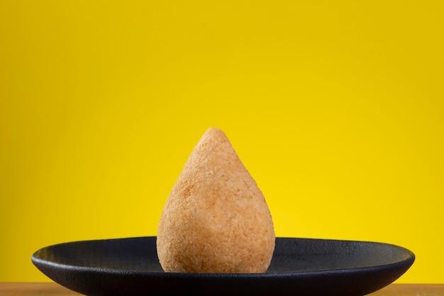 Gebratener coxinha auf schwarzem teller mit gelbem hintergrund.