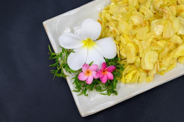 Gebratener durian mit blumen und blättern in der schale auf dem tisch
