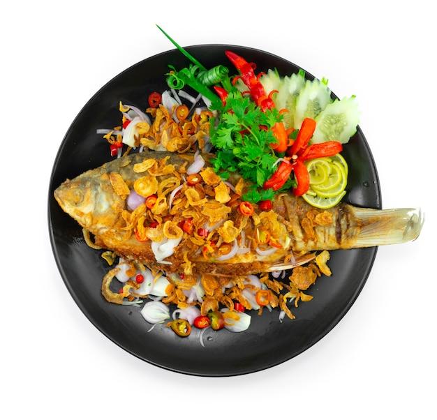 Gebratener eingelegter fisch, saurer geschmack auf knuspriger schalotte, chili und limette thai food local dish style dekoration schnitzen von chili und gemüse draufsicht