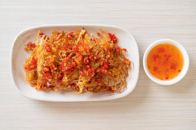 Gebratener enoki-pilz oder goldener nadelpilz mit salz und chili. vegane und vegetarische küche